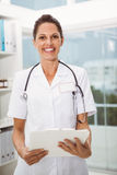 Confident female doctor holding clipboard in medical office Stock Images