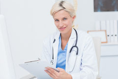 Confident female doctor holding clipboard Stock Image