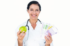 Confident female doctor holding green apple and banknotes Royalty Free Stock Photo