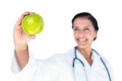 Confident female doctor holding green apple Stock Image