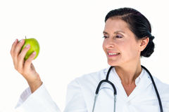 Confident female doctor holding green apple Royalty Free Stock Photography
