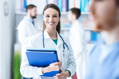 Confident female doctor holding medical records. Confident attractive female doctor in the office holding medical records and folders, she is smiling at camera Stock Photos