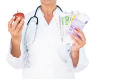 Confident female doctor holding red apple and banknotes Royalty Free Stock Photography