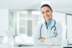 Confident female doctor at office desk Stock Photos