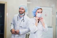 Confident female doctor putting on medical face mask while preparing for operation, her male colleague standing behind. Confident Vietnamese doctor putting on Stock Photography