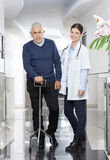Confident Female Doctor With Senior Man Using Cane Royalty Free Stock Photos