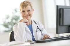 Confident Female Doctor Sitting At Computer Desk Stock Images