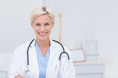 Confident female doctor smiling in clinic Stock Image