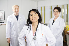 Confident Female Doctor Smiling While Standing With Colleagues. Portrait of confident female doctor smiling while standing with colleagues in clinic stock images