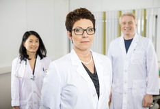 Confident Female Doctor Standing With Colleagues In Hospital stock photography