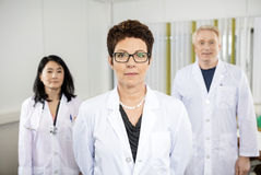 Confident Female Doctor Standing With Colleagues Royalty Free Stock Image