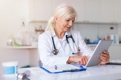 Female doctor using digital tablet in her office royalty free stock photography
