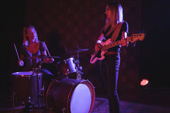 Confident female drummer and guitarist performing on illuminated stage. In nightclub Royalty Free Stock Photos