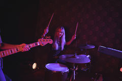 Confident female drummer looking at guitarist while performing on stage. In nightclub Stock Images