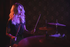 Confident female drummer performing on illuminated stage Royalty Free Stock Photo