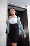 Confident Female Entrepreneur. Low angle view of confident female entrepreneur stepping out of elevator Stock Photo