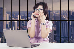 Confident female entrepreneur with laptop and smartphone Royalty Free Stock Image