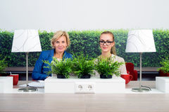 Confident Female Environmentalists Sitting At Desk Royalty Free Stock Images