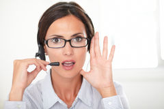 Confident female executive conversing on headset Stock Photography