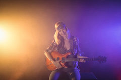 Confident female guitarist performing in music concert Stock Photo