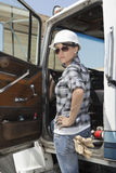 Confident female industrial worker standing by vehicle door with hand on hip Stock Images