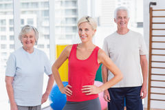 Confident female instructor with senior couple Royalty Free Stock Photo