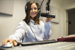 Confident Female Jockey Using Technologies In Radio Studio Stock Photos