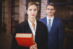 Confident female lawyer with businessman in office. Portrait of confident female lawyer with businessman standing in office stock photography