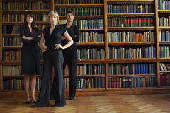 Confident Female Lawyers In Library. Three confident female lawyers standing in library Royalty Free Stock Images