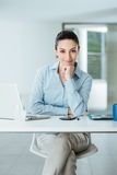 Confident female manager at desk posing Stock Photography