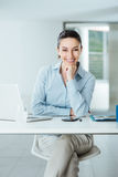 Confident female manager at desk posing. Beautiful confident female manager sitting at office desk and smiling at camera with hand on chin, room interior on Stock Image