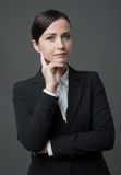Confident female manager with hand on chin. Confident charming female manager with hand on chin posing on gray background Stock Images