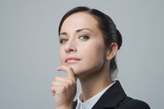 Confident female manager with hand on chin Stock Photos
