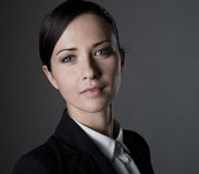Confident female manager posing on dark background Stock Images