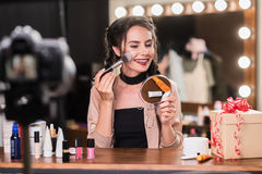 Confident female model using cosmetics in front of camera Royalty Free Stock Photo