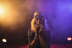 Confident female musician playing harmonica in illuminated nightclub Stock Photo