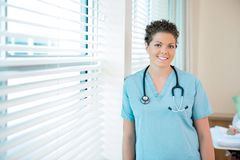 Confident Female Nurse With Stethoscope Around Stock Photo