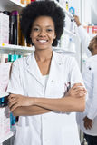 Confident Female Pharmacist With Arms Crossed In Pharmacy royalty free stock images