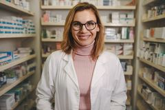 Confident female pharmacist on drug store stock photography