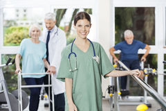 Confident Female Physiotherapist Standing In Rehab Center. Portrait of confident female physiotherapist standing with doctor and patients in background at rehab Stock Images