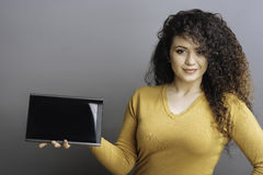 Confident female presenting new tablet Stock Photo