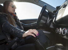 Confident female racer drives car Stock Images