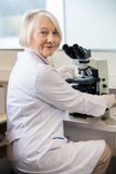 Confident Female Scientist Using Microscope In Lab Stock Photos