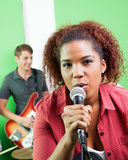 Confident Female Singer Holding Microphone At Recording Studio. Portrait of confident female singer holding microphone while guitarist performing in background Stock Images