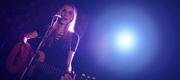 Confident female singer performing with guitar in nightclub Royalty Free Stock Photography