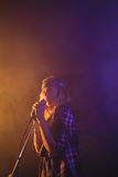 Confident female singer performing in music concert Royalty Free Stock Image
