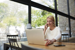 Confident female speaking on mobile phone with while sitting at wooden table with open laptop computer Royalty Free Stock Photos