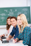 Confident Female Student With Classmates At Desk Royalty Free Stock Photo
