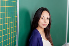 Confident female student leaning against board Royalty Free Stock Photography