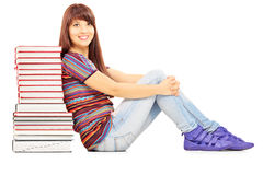 Confident female student leaning on a pile of books. Isolated on white background Stock Image